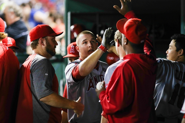 Jul 30, 2013; Arlington, TX, USA; Los Angeles Angels center fielder Mike Trout (27) celebrates with teammates in the dugout after scoring during the seventh inning against the Texas Rangers at Rangers Ballpark in Arlington. Mandatory Credit: Kevin Jairaj-USA TODAY Sports