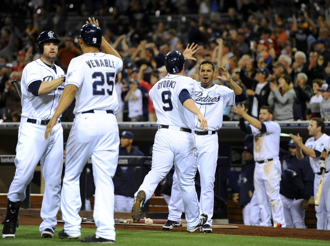 Jul 30, 2013; San Diego, CA, USA; San Diego Padres third baseman Chase Headley (far left) and left fielder Jesus Guzman (right) congratulate right fielder Will Venable (25) and second baseman Jedd Gyorko (9) after they scored on a two-run double by catcher Nick Hundley (not pictured) during the eighth inning against the Cincinnati Reds at Petco Park. Mandatory Credit: Christopher Hanewinckel-USA TODAY Sports