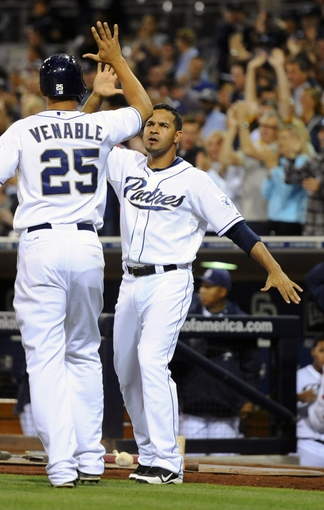 Jul 30, 2013; San Diego, CA, USA; San Diego Padres right fielder Will Venable (25) is congratulated by left fielder Jesus Guzman (15) after scoring during the eighth inning against the Cincinnati Reds at Petco Park. Mandatory Credit: Christopher Hanewinckel-USA TODAY Sports
