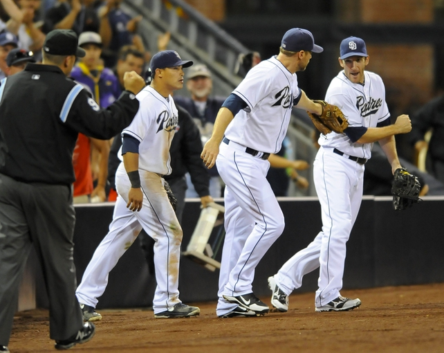 Jul 30, 2013; San Diego, CA, USA; San Diego Padres third baseman Chase Headley (center) celebrates with Chris Denorfia (13) and shortstop Everth Cabrera (2) after making the final out of the game against the Cincinnati Reds at Petco Park. The Padres won 4-2. Mandatory Credit: Christopher Hanewinckel-USA TODAY Sports