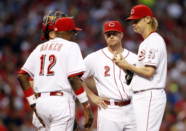 Aug 2, 2013; Cincinnati, OH, USA; Cincinnati Reds manager Dusty Baker (12) goes to the mound to relieve starting pitcher Bronson Arroyo (61) during the fourth inning against the St. Louis Cardinals at Great American Ball Park. Mandatory Credit: Frank Victores-USA TODAY Sports