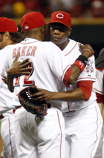 Aug 3, 2013; Cincinnati, OH, USA; Cincinnati Reds relief pitcher Aroldis Chapman (54) is congratulated by manager Dusty Baker (12) after the Reds beat the St. Louis Cardinals 8-3 at Great American Ball Park. Mandatory Credit: David Kohl-USA TODAY Sports