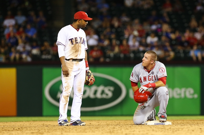 Jul 30, 2013; Arlington, TX, USA; Texas Rangers shortstop Elvis Andrus (left) speaks with Los Angeles Angels center fielder Mike Trout (right) during the game at Rangers Ballpark in Arlington. Texas won 14-11.  Mandatory Credit: Kevin Jairaj-USA TODAY Sports