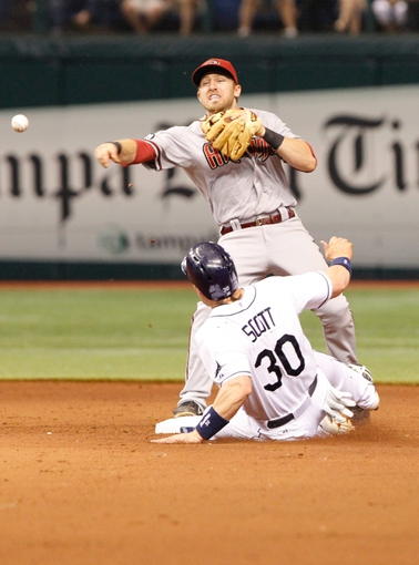 Jul 30, 2013; St. Petersburg, FL, USA; Arizona Diamondbacks shortstop Cliff Pennington (4) forces out Tampa Bay Rays designated hitter Luke Scott (30) and throws the ball to first for a double play during the seventh inning at Tropicana Field. Mandatory Credit: Kim Klement-USA TODAY Sports