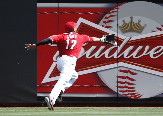 Aug 4, 2013; Cincinnati, OH, USA; Cincinnati Reds center fielder Shin-Soo Choo (17) reaches for a ball during the ninth inning against the St. Louis Cardinals at Great American Ball Park. The Cardinals defeated the Reds 15-2. Mandatory Credit: Frank Victores-USA TODAY Sports