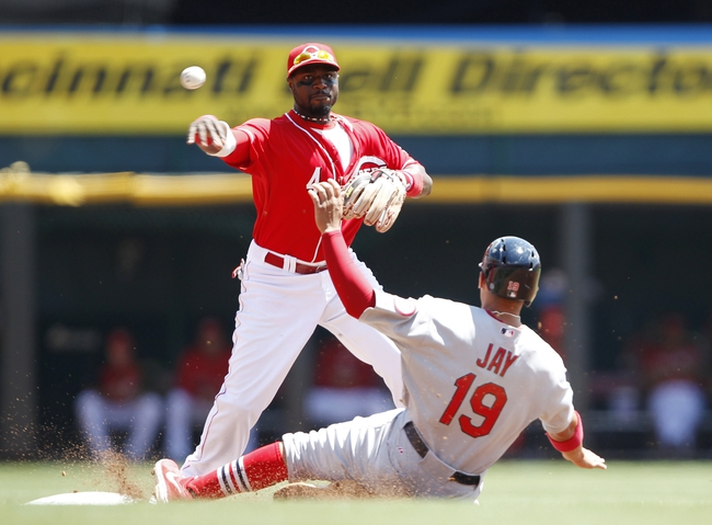 Aug 4, 2013; Cincinnati, OH, USA; Cincinnati Reds second baseman Brandon Phillips (4) turns a double play during the third inning against the St. Louis Cardinals center fielder Jon Jay (19) at Great American Ball Park. Mandatory Credit: Frank Victores-USA TODAY Sports