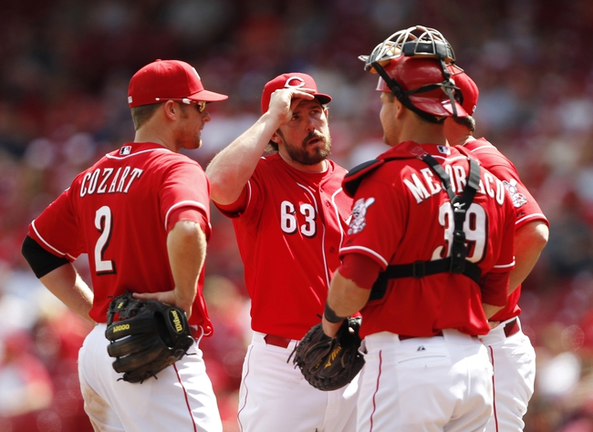 Aug 4, 2013; Cincinnati, OH, USA; Cincinnati Reds relief pitcher Sam LeCure (63) has a meeting on the mound with catcher Devin Mesoraco (39) and shortstop Zack Cozart (2) and pitching coach Bryan Price (right) during the ninth inning against the St. Louis Cardinals at Great American Ball Park. The Cardinals defeated the Reds 15-2. Mandatory Credit: Frank Victores-USA TODAY Sports