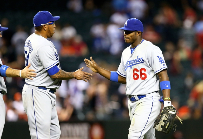 Jul. 9, 2013; Phoenix, AZ, USA: Los Angeles Dodgers pitcher Ronald Belisario (left) high fives outfielder Yasiel Puig against the Arizona Diamondbacks at Chase Field. Mandatory Credit: Mark J. Rebilas-USA TODAY Sports