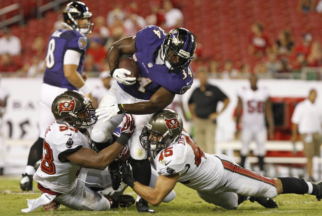 Aug 8, 2013; Tampa, FL, USA; Baltimore Ravens defensive back Mo Lee (34) gets tackled by Tampa Bay Buccaneers linebacker Najee Goode (53) and linebacker Dom DeCicco (45) during the second half at Raymond James Stadium. Mandatory Credit: Kim Klement-USA TODAY Sports