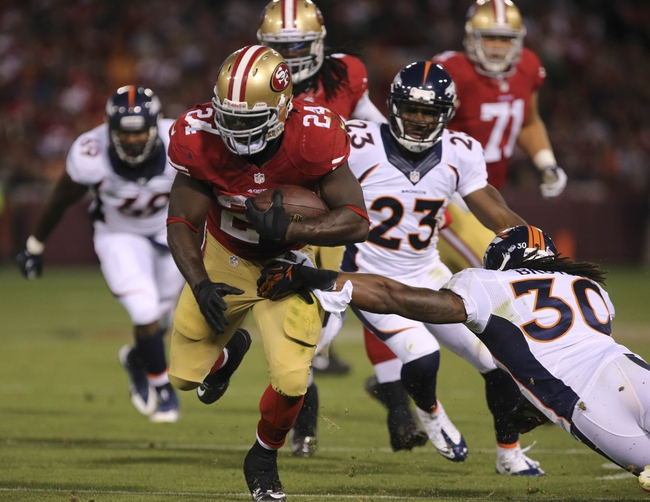 Aug 8, 2013; San Francisco, CA, USA; Denver Broncos strong safety David Bruton (30) gets an arm on San Francisco 49ers running back Anthony Dixon (24) before the play is called back on a penalty during the fourth quarter at Candlestick Park. The Denver Broncos defeated the San Francisco 49ers 10-6. Mandatory Credit: Kelley L Cox-USA TODAY Sports