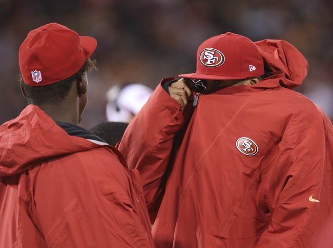 Aug 8, 2013; San Francisco, CA, USA; San Francisco 49ers quarterback Colin Kaepernick (7) zips up his jacket on the sideline with linebacker Aldon Smith (99) during the fourth quarter against the Denver Broncos at Candlestick Park. The Denver Broncos defeated the San Francisco 49ers 10-6. Mandatory Credit: Kelley L Cox-USA TODAY Sports