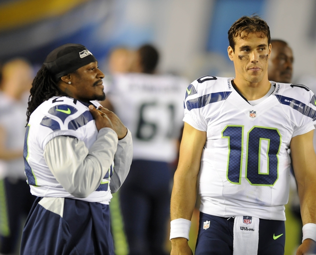 Aug 8, 2013; San Diego, CA, USA; Seattle Seahawks quarterback Brady Quinn (10) talks with Seattle running back Marshawn Lynch (24) on the sidelines during the second half against the San Diego Chargers at Qualcomm Stadium. Mandatory Credit: Christopher Hanewinckel-USA TODAY Sports