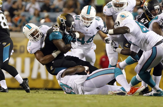 Aug 9, 2013; Jacksonville, FL, USA; Miami Dolphins outside linebacker Alonzo Highsmith (45) tackles Jacksonville Jaguars running back De'Leon Eskridge (39) during the second half at EverBank Field. Miami Dolphins defeated the Jacksonville Jaguars 27-3. Mandatory Credit: Kim Klement-USA TODAY Sports