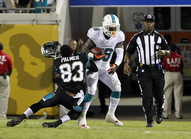 Aug 9, 2013; Jacksonville, FL, USA; Miami Dolphins wide receiver Chad Bumphis (16) runs with the ball as Jacksonville Jaguars wide receiver Tobais Palmer (83) tackles and loses his helmet during the second half at EverBank Field. Miami Dolphins defeated the Jacksonville Jaguars 27-3. Mandatory Credit: Kim Klement-USA TODAY Sports