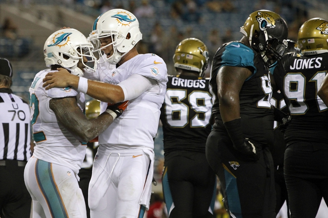 Aug 9, 2013; Jacksonville, FL, USA; Miami Dolphins running back Jonas Gray (32) is congratulated by quarterback Pat Devlin (7) after he scored a touchdown during the second half against the Jacksonville Jaguars at EverBank Field. Miami Dolphins defeated the Jacksonville Jaguars 27-3. Mandatory Credit: Kim Klement-USA TODAY Sports