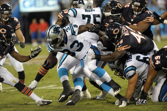 Aug 9, 2013; Charlotte, NC, USA; Carolina Panthers running back Tauren Poole (33) runs through the line as he is pursued by Chicago Bears linebacker Lawrence Wilson (49) and defensive tackle Christian Tupou (64) while playing at Bank of America Stadium.  Carolina wins 24-17. Mandatory Credit: Sam Sharpe-USA TODAY Sports