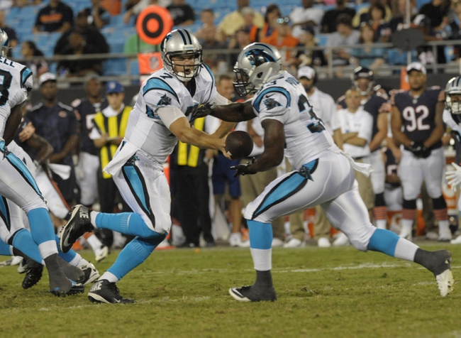 Aug 9, 2013; Charlotte, NC, USA; Carolina Panthers quarterback Jimmy Clausen (7) hands off to running back Tauren Poole (33) while playing against the Chicago Bears at Bank of America Stadium.  Carolina wins 24-17. Mandatory Credit: Sam Sharpe-USA TODAY Sports