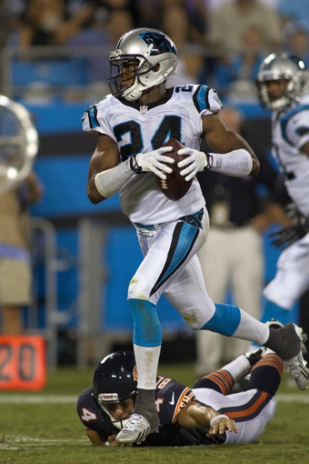 Aug 9, 2013; Charlotte, NC, USA; Carolina Panthers cornerback Josh Norman (24) returns an interception for a touchdown during the second half against the Chicago Bears. The Panthers defeated the Bears 24-17. Mandatory Credit: Jeremy Brevard-USA TODAY Sports