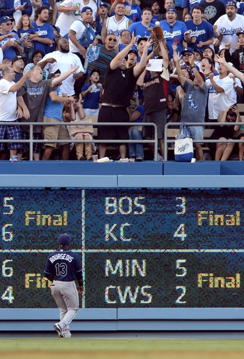 Aug 11, 2013; Los Angeles, CA, USA;   Fans catch the home run ball of Los Angeles Dodgers second baseman Mark Ellis (not pictured) in the sixth inning as Tampa Bay Rays left fielder Jason Bourgeois (13) looks on at Dodger Stadium. Mandatory Credit: Jayne Kamin-Oncea-USA TODAY Sports