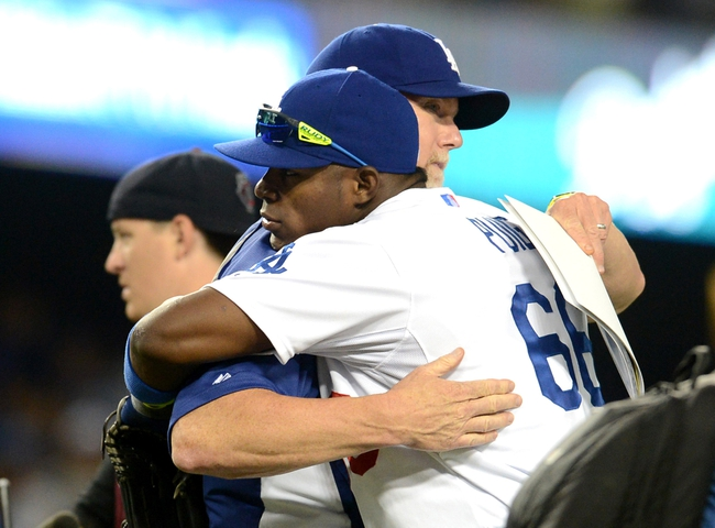 Aug 11, 2013; Los Angeles, CA, USA;   Los Angeles Dodgers right fielder Yasiel Puig (66) gets a hug from batting coach Mark McGwire (12) at the end of the game against the Tampa Bay Rays at Dodger Stadium. Dodgers won 8-2. Mandatory Credit: Jayne Kamin-Oncea-USA TODAY Sports