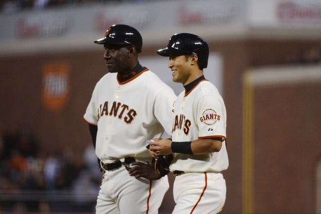 July 9, 2013; San Francisco, CA, USA; San Francisco Giants left fielder Kensuke Tanaka (37, right) smiles after recording his first MLB hit on a single during the fifth inning against the New York Mets at AT&T Park. Also pictured: San Francisco Giants first base coach Roberto Kelly (39, left). Mandatory Credit: Kyle Terada-USA TODAY Sports