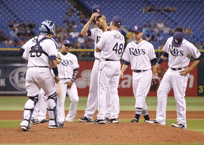Aug 14, 2013; St. Petersburg, FL, USA; Tampa Bay Rays starting pitcher David Price (14) reacts after he gave up 3 runs as he talks with  pitching coach Jim Hickey (48) on the mound during the fifth inning against the Seattle Mariners at Tropicana Field. Mandatory Credit: Kim Klement-USA TODAY Sports