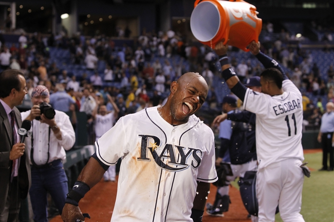 Aug 14, 2013; St. Petersburg, FL, USA; Tampa Bay Rays left fielder Jason Bourgeois (13) reacts after he got a gatorade bath by teammate shortstop Yunel Escobar (11) as he gets interview by sunsports announcer Todd Kalas after he hit the game winning RBI single against the Seattle Mariners at Tropicana Field. Tampa Bay Rays defeated the Seattle Mariners 5-4. Mandatory Credit: Kim Klement-USA TODAY Sports