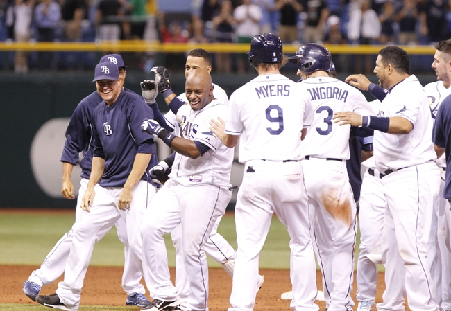Aug 14, 2013; St. Petersburg, FL, USA; Tampa Bay Rays left fielder Jason Bourgeois (13) is congratulated by teamamtes after he hit the game winning RBI single during the ninth inning against the Seattle Mariners at Tropicana Field. Tampa Bay Rays defeated the Seattle Mariners 5-4. Mandatory Credit: Kim Klement-USA TODAY Sports