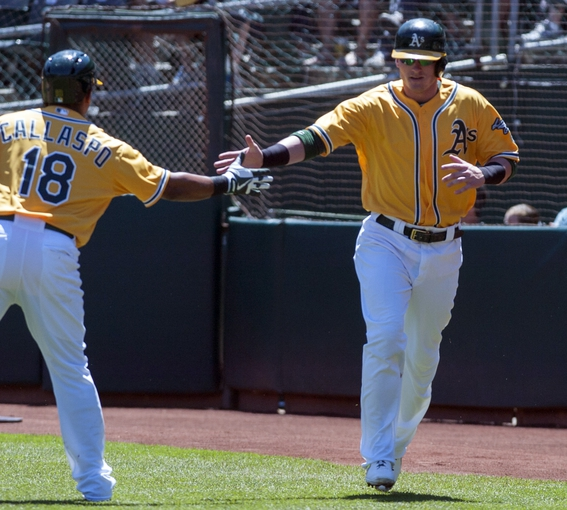 Aug 15, 2013; Oakland, CA, USA; Oakland Athletics second baseman Alberto Callaspo (18) high fives third baseman Josh Donaldson (20) after he scored against the Houston Astros during the first inning at O.Co Coliseum. Mandatory Credit: Ed Szczepanski-USA TODAY Sports