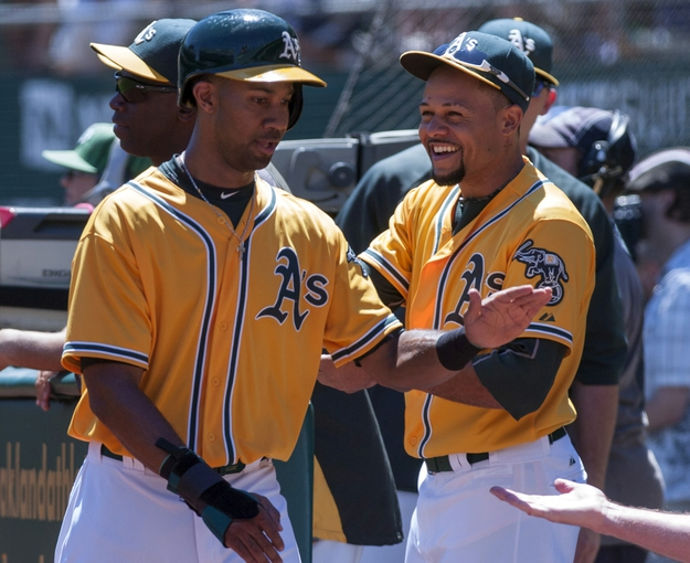 Aug 15, 2013; Oakland, CA, USA; Oakland Athletics center fielder Chris Young (25) high fives team mates after scoring against the Houston Astros during the first inning at O.Co Coliseum. Mandatory Credit: Ed Szczepanski-USA TODAY Sports