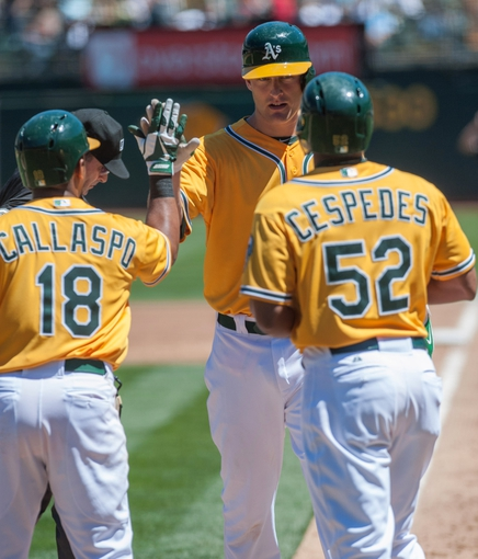 Aug 15, 2013; Oakland, CA, USA; Oakland Athletics second baseman Alberto Callaspo (18) and left fielder Yoenis Cespedes (52) congratulate first baseman Nate Freiman (7) after he hit a home run against the Houston Astros during the third inning at O.Co Coliseum. Mandatory Credit: Ed Szczepanski-USA TODAY Sports