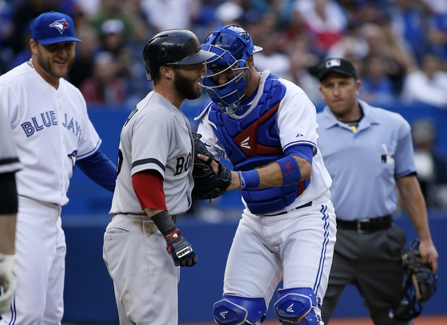 Aug 15, 2013; Toronto, Ontario, CAN; Boston Red Sox second baseman Dustin Pedroia (left) gets tagged by Toronto Blue Jays catcher J.P. Arencibia (9) at home plate as Toronto Blue Jays pitcher Mark Buehrle (56) looks on  in the first inning at the Rogers Centre. Mandatory Credit: John E. Sokolowski-USA TODAY Sports