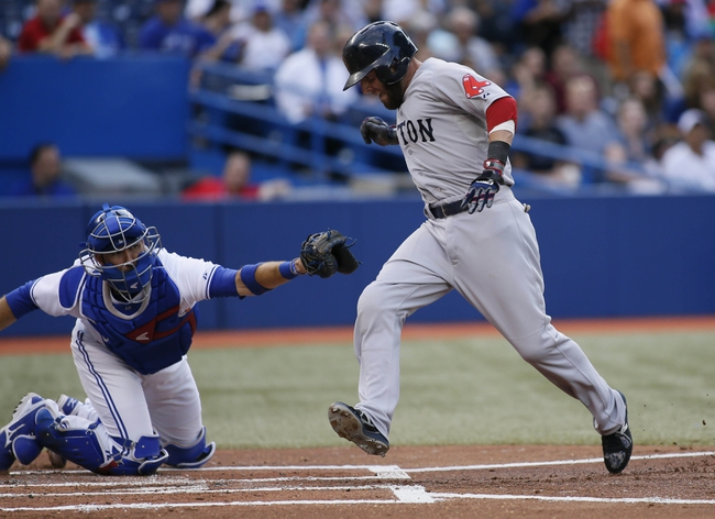 Aug 15, 2013; Toronto, Ontario, CAN; Boston Red Sox second baseman Dustin Pedroia (right) tries to avoid a tag by Toronto Blue Jays catcher J.P. Arencibia (9) in the first inning at the Rogers Centre. Mandatory Credit: John E. Sokolowski-USA TODAY Sports