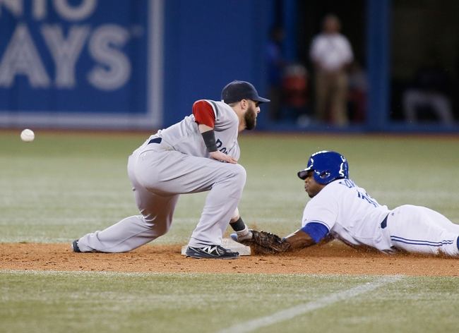 Aug 15, 2013; Toronto, Ontario, CAN; Toronto Blue Jays centre fielder Rajai Davis (11) slides into second base as the ball gets past Boston Red Sox second baseman Dustin Pedroia (15) in the eighth inning at the Rogers Centre. Toronto defeated Boston 2-1. Mandatory Credit: John E. Sokolowski-USA TODAY Sports