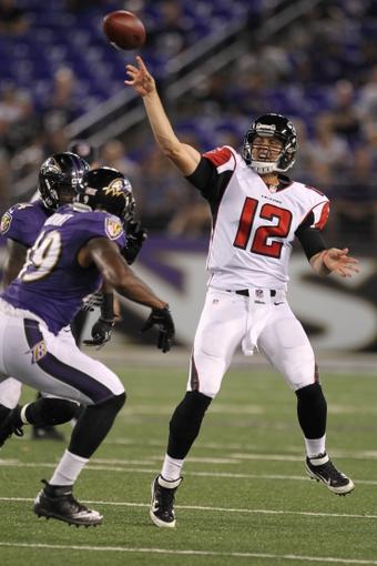 Aug 15, 2013; Baltimore, MD, USA; Atlanta Falcons quarterback Sean Renfree (12) throws the ball under pressure by the Baltimore Ravens defense at M&T Bank Stadium. Mandatory Credit: Mitch Stringer-USA TODAY Sports