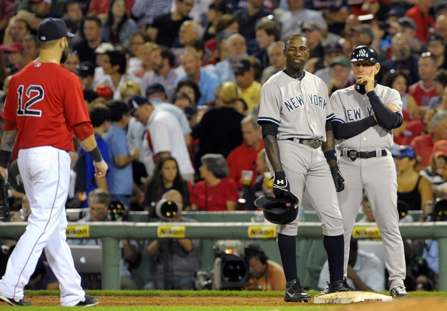 Aug 16, 2013; Boston, MA, USA; New York Yankees left fielder Alfonso Soriano (12) winks at Boston Red Sox first baseman Mike Napoli (12) during the seventh inning at Fenway Park. Mandatory Credit: Bob DeChiara-USA TODAY Sports