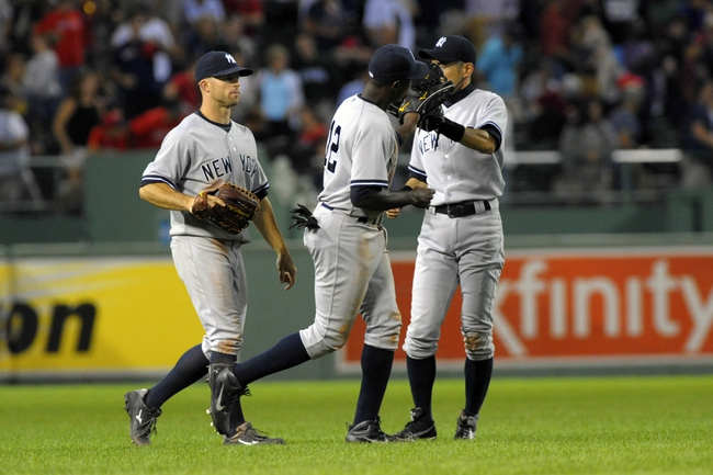 Aug 16, 2013; Boston, MA, USA; New York Yankees center fielder Brett Gardner (left) left fielder Alfonso Soriano (12) and right fielder Ichiro Suzuki (31) celebrate their victory over the Boston Red Sox at Fenway Park. Mandatory Credit: Bob DeChiara-USA TODAY Sports
