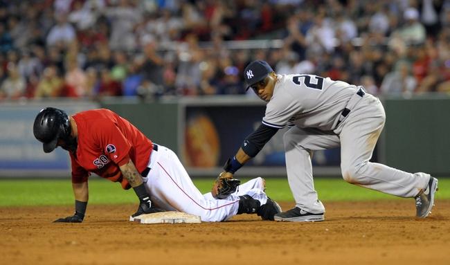Aug 16, 2013; Boston, MA, USA; Boston Red Sox first baseman Mike Napoli (12) slides past New York Yankees second baseman Robinson Cano (24) during the ninth inning at Fenway Park. Mandatory Credit: Bob DeChiara-USA TODAY Sports
