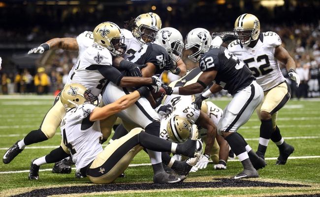 Aug 16, 2013; New Orleans, LA, USA; Oakland Raiders running back Jamize Olawale (49) is tackled in the end zone by New Orleans Saints outside linebacker Will Herring (bottom left) and free safety Isa Abdul-Quddus (left) and other Saints defenders for a safety in the second half at the Mercedes-Benz Superdome.  New Orleans defeated Oakland 28-20. Mandatory Credit: Crystal LoGiudice-USA TODAY Sports