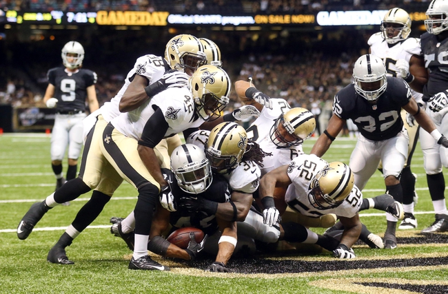 Aug 16, 2013; New Orleans, LA, USA; Oakland Raiders running back Jamize Olawale (49) is tackled in the end zone by New Orleans Saints defensive back Jerico Nelson (37) and other Saints defenders for a safety in the second half at the Mercedes-Benz Superdome. New Orleans defeated Oakland 28-20. Mandatory Credit: Crystal LoGiudice-USA TODAY Sports