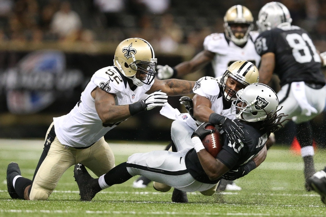 Aug 16, 2013; New Orleans, LA, USA; Oakland Raiders wide receiver Greg Jenkins (10) is tackled by New Orleans Saints inside linebacker Kevin Reddick (52) and cornerback Dion Turner (right) in the second half at the Mercedes-Benz Superdome. New Orleans defeated Oakland 28-20.  Mandatory Credit: Crystal LoGiudice-USA TODAY Sports