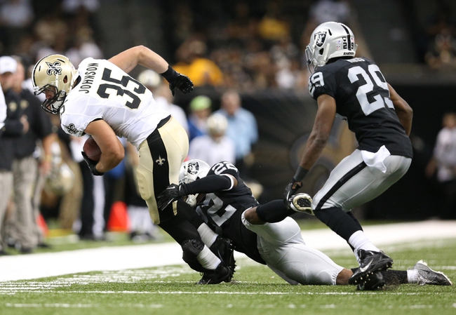 Aug 16, 2013; New Orleans, LA, USA; New Orleans Saints fullback Austin Johnson (35) is tackled by Oakland Raiders defensive back Taiwan Jones (22) in the second half at the Mercedes-Benz Superdome. New Orleans defeated Oakland 28-20.Mandatory Credit: Crystal LoGiudice-USA TODAY Sports
