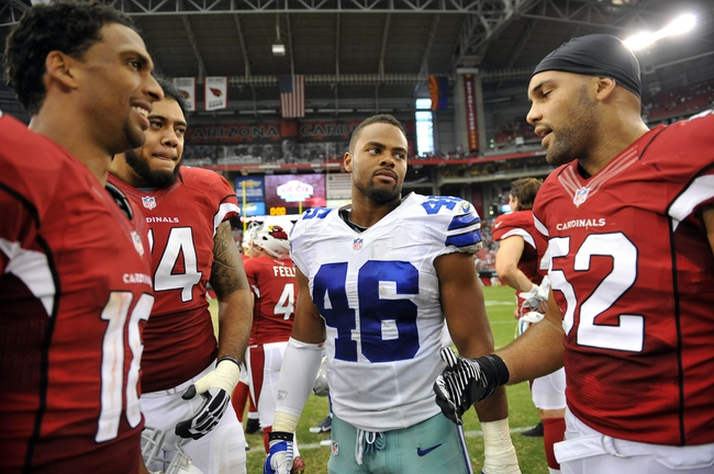 August 17, 2013; Phoenix, AZ, USA; Dallas Cowboys outside linebacker Brandon Magee (46) meets with Arizona Cardinals linebacker Colin Parker (52), wide receiver Kerry Taylor (18) and guard Senio Kelemete (64) following the 12-7 loss at University of Phoenix Stadium. Mandatory Credit: Gary A. Vasquez-USA TODAY Sports