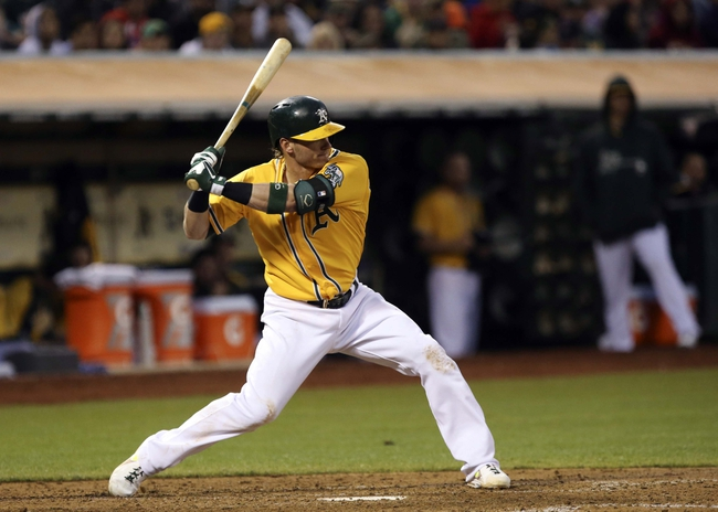 Aug 17, 2013; Oakland, CA, USA; Oakland Athletics third baseman Josh Donaldson (20) hits a single to break up the no-hitter by Cleveland Indians starting pitcher Ubaldo Jimenez (not pictured) during the sixth inning at O.co Coliseum. Mandatory Credit: Kelley L Cox-USA TODAY Sports