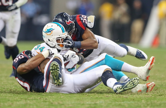 Aug 17, 2013; Houston, TX, USA; Miami Dolphins running back Marcus Thigpen (34) is tackled by Houston Texans safety Jawanza Starling (29) and linebacker Cameron Collins (90) during the game at Reliant Stadium. The Texans defeated the Dolphins 24-17. Mandatory Credit: Kevin Jairaj-USA TODAY Sports