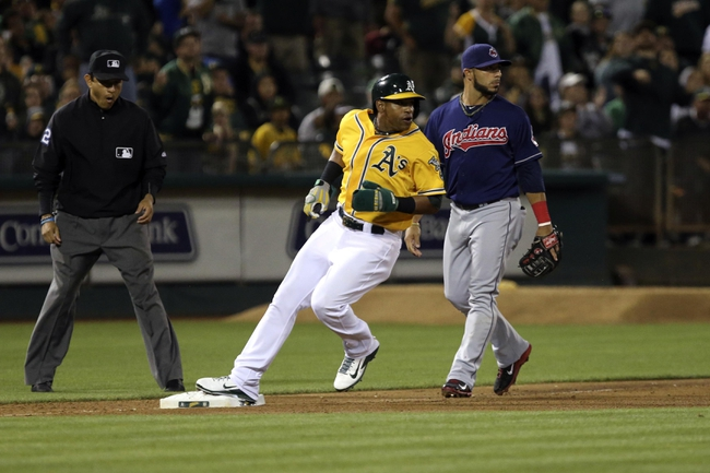 Aug 17, 2013; Oakland, CA, USA; Oakland Athletics center fielder Yoenis Cespedes (52) follows the ball as he reaches the base against Cleveland Indians third baseman Mike Aviles (4) during the eighth inning at O.co Coliseum. Mandatory Credit: Kelley L Cox-USA TODAY Sports