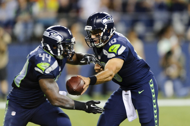 Aug 17, 2013; Seattle, WA, USA; Seattle Seahawks quarterback Brady Quinn (10) hands the ball off to running back Spencer Ware (44) during the 2nd half against the Denver Broncos at CenturyLink Field. Seattle defeated Denver 40-10. Mandatory Credit: Steven Bisig-USA TODAY Sports