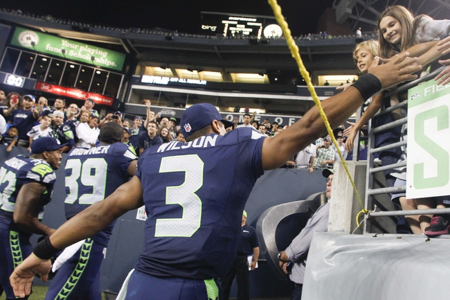 Aug 17, 2013; Seattle, WA, USA; Seattle Seahawks quarterback Russell Wilson (3) greets fans after a 40-10 preseason victory over the Denver Broncos at CenturyLink Field. Mandatory Credit: Joe Nicholson-USA TODAY Sports
