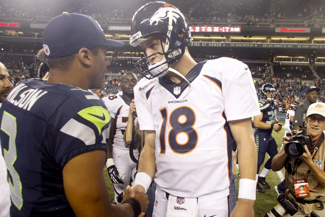 Aug 17, 2013; Seattle, WA, USA; Seattle Seahawks quarterback Russell Wilson (3) and Denver Broncos quarterback Peyton Manning (18) speak following a 40-10 preseason victory by the Seahawks at CenturyLink Field. Mandatory Credit: Joe Nicholson-USA TODAY Sports