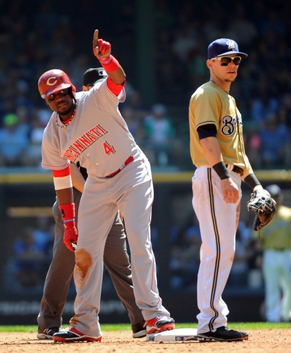 Aug 18, 2013; Milwaukee, WI, USA; Cincinnati Reds second baseman Brandon Phillips (left) reacts next to Milwaukee Brewers second baseman Scooter Gennett (right) after hitting a double to drive in two runs in the second inning at Miller Park. Mandatory Credit: Benny Sieu-USA TODAY Sports